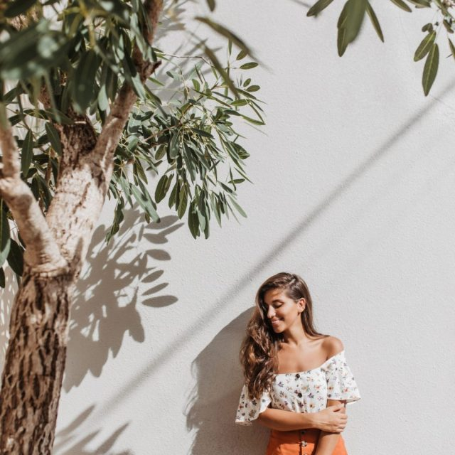 Portrait of charming lady in summer resort outfit posing next to olive tree on white background.